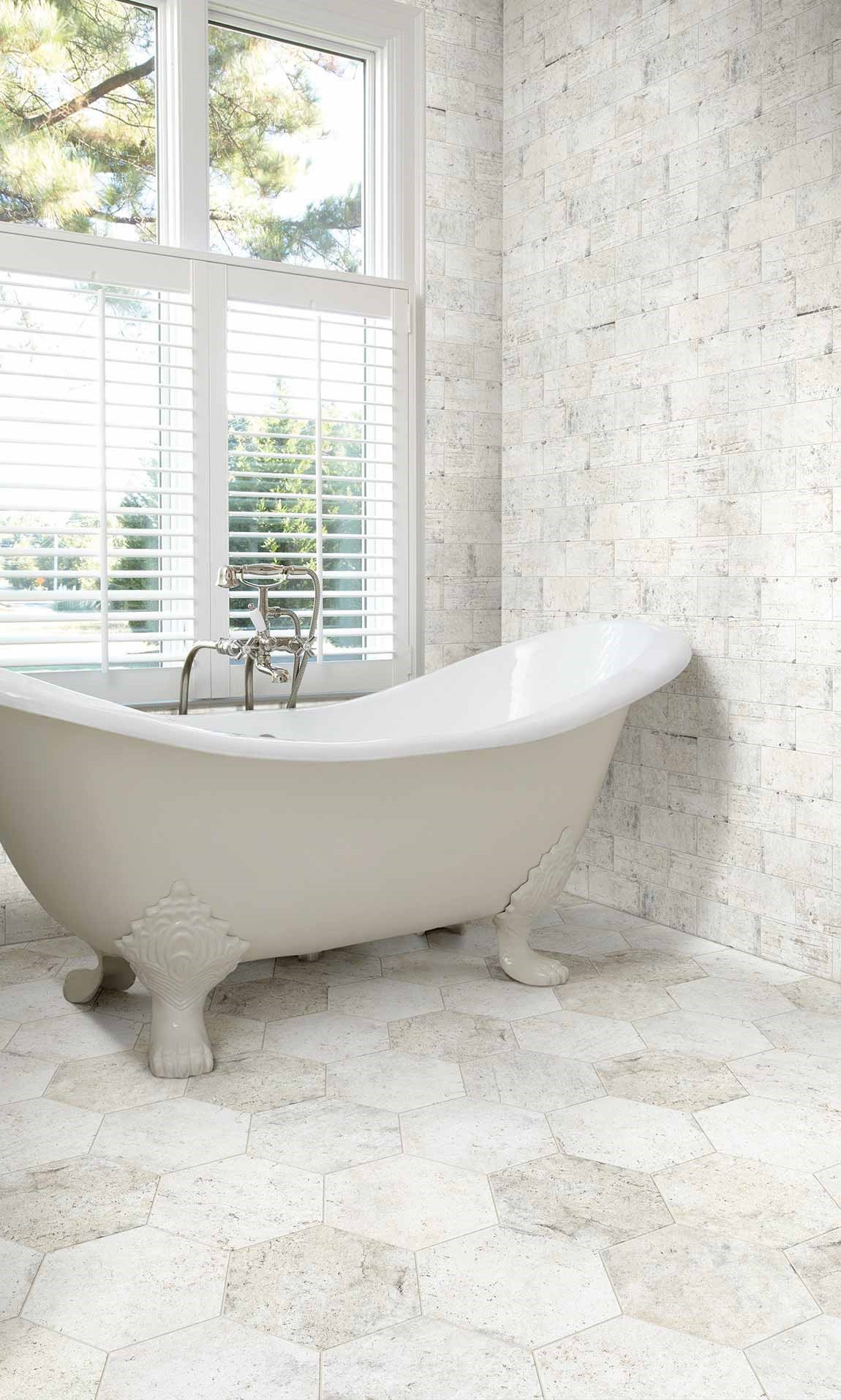 freestanding bathtub in light colored bathroom with ceramic tile